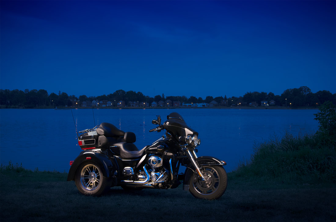 A black Harley-Davidson trike is photographed against a blue lake in Peterborough Ontario.